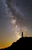 Silhouette of a man on a mountain under the Milky Way on the Lago-Naki plateau in Russia.
