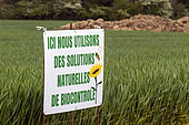 Organic information on a sign in a cereal field in spring by a country lane, Belleville area, Lorraine, France