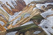 Rhyolite mountains partly covered with moss and snow, in Landmannalaugar, Fjallabak Nature Reserve, Iceland, Europe