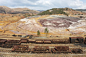 Disused wagons at the dramatically scarred landscape of mineral-rich ground and rock at the Rio Tinto mines. Huelva province, Andalusia, Spain.