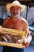 IN*Montenegro, homme tenant un cageot de poissons