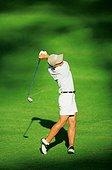 IN*Vue plongeante sur joueuse de golf sur green, en fin de drive, chemise et bermuda blancs