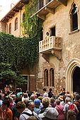 Tourists gather in the courtyard of Juliet's house and a young lady stands on the famous balcony. In fact the building was 'creatively' restored in the 1930s to create its current romantic appearence. Verona, Veneto, Italy
