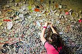 A girl leaves a love message at the entrance to Juliet's House, Verona, Veneto, Italy