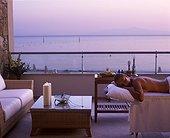 IN*Grèce, Paros, femme allongée sur table de massage sur balcon d'une suite de l'hôtel Asterias, mer au fond, coucher de soleil