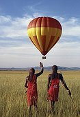 Kenya;Narok;Masai Mara - Two Maasai warriors watch a hot air balloon flight over Masai Mara.