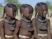 Namibia;Kaokoland - Three young girls, their bodies lightly smeared with a mixture of red ochre, butterfat and herbs, wear round white-beaded necklaces, called ombwari, a tradition of all Himba people. Their other neck ornaments, eha, are made of le [...]