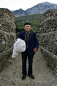 A serene old farmer poses for a portrait just before crossing a bridge made of ropes and wood over the River Vjosa, Valley of Permet, Albania
