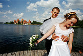 Trakai, Lithuania: just married posing in front of the insular castle (Traku pilis)
