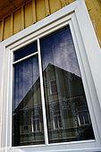 Trakai, Lithuania. A typical karaim house reflecting on window of another karaim house in Karaimu gatvè (Karaims street)