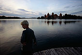 Trakai, Lithuania: a boy fishing in the Galves lake at dusk;
