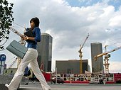 A Chinese young woman walks on a street as a building construction is seen in the background in the Central Business District (CBD) in Beijing.