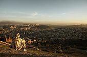 Man in traditional djellaba looks over the city of Fes at sunset, Fes, Morocco
