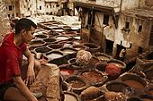 Young tannery worker looking over the tanneries, Fes, Morocco