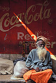 A Sadu (holy man) sits in stark contrast with the ad behind him in the alleys of Varanasi.