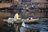 A man selling flower gifts to the Ganges river on his little boat, entirely made by plastic bottleskept together by a fishing net. In the background one of Varanasi's burning ghats.