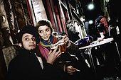 Italia,Venezia -  locale tipico  2 ragazzi  bevono lo spritz, aperitivo tradizionale ( vino bianco allungato e reso frizzante con acqua minerale e colorato con Aperol o Campari)