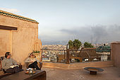 Roof terrace and view towards potteries (smoke), Riad Larrousa, traditional Moroccan riad, Fes, Morocco. Property released.