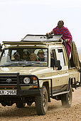 Masai guide with tourists on a tour of the savanna