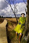 IN*Jeune femme posant appuyée contre arbre, manteau vert, bottes
