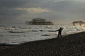 Boy throwing a stone into the sea on Brighton beach