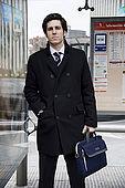 Giovane uomo d'affari in Paseo de la Castellana alla fermata dell'autobus, Castellana, Madrid, Espagne