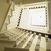 Above view of a winding staircase with a glass skylight at the top,