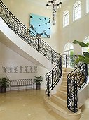 Elegant curving staircase with wrought iron banister railings in spacious hallway