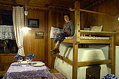 Nicole, daughter of Sergio and Manuela Rossi, on the traditional 'stufa' stove at Rifugio Fuciade, Trentino, Italy
