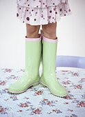 A girl standing on a table wearing spotty green boots