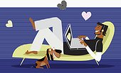 Hearts around man using laptop on chaise lounge