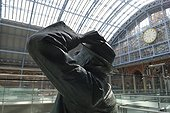 England, London, St Pancras Station. A statue of poet John Betjeman by Martin Jennings at St. Pancras International station, with the famous clock in the background.