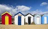 England, Suffolk, Southwold. A line of colourful beach huts on the beach at Southwold.