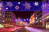 England, London, Regent Street. Light rails from traffic as it passes along Regent Street under the annual Christmas lights.