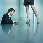 Man sitting at table working on laptop, woman standing on table