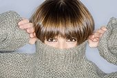 Close-up of a young woman covering her face in turtleneck