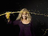 Woman throwing orange juice from a glass