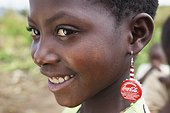 A Girl Wearing Coca-Cola Bottle Cap Earrings; Manica, Mozambique, Africa