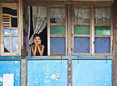 A Boy Looks Out The Window Of His House; Prabumulih Timur Sumatera Selatan Indonesia