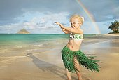 Hawaii, Oahu, Young girl in a hula skirt dancing on the beach, rainbow in background.