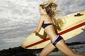 Hawaii, Kauai, Kealia Beach, Surfer girl enjoying a day out.