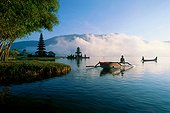Indonesia, Bali, Ulu Danu temple at sunrise, small boats on water, fog