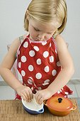 Little girl greasing small casserole dish