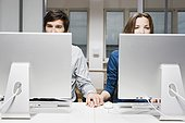 young couple sitting behind computers in office holding hands