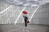 businessman with red suitcase and umbrella jumping