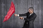 businessman trying to hold red umbrella in stormy weather