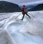 Mountaineer standing over a brook