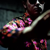 A man wearing a colourful shirt and pushing the camera away