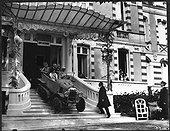 Image Exclusive * Employés de l'Hôtel Regina à Arcachon observant des clients sortir de celui-ci en autochenille type A en 1921.