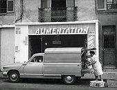 Image Exclusive * Femme chargeant des caisses dans une fourgonnette Panhard PL17 F50 type WL2 en 1960.
